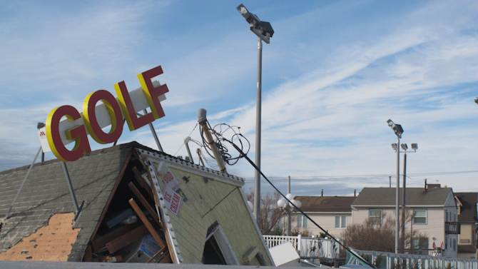 In a Nov. 1, 2012 photo, a mini-golf course is among the boardwalk attractions in Point Pleasant Beach, N.J. that were damaged by Superstorm Sandy. Point Pleasant Beach has reached an agreement with the owners of Jenkinson's Boardwalk to drop a proposed midnight bar closing law in return for the company dropping lawsuits against the town. Jenkinson's also will contribute up to $1 million to help rebuild the storm-damaged boardwalk. (AP Photo/Wayne Parry)