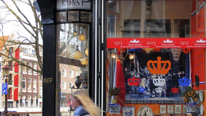 A woman pedals past a shop window decorated with the color of the House of Orange and a picture of the King-to-be Willem-Alexander and his wife Princess Maxima in Amsterdam, Netherlands Wednesday, April 24, 2013. Queen Beatrix has announced she will relinquish the crown on April 30, 2013, after 33 years of reign, leaving the monarchy to her son Crown Prince Willem Alexander. (AP Photo/Margriet Faber)