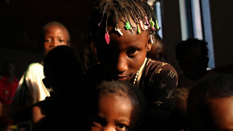 Children look on, at a temporary IDP camp in Bangui