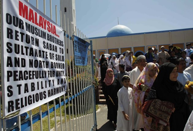Muslim residents walk past signs displayed at the gate of Blue Mosque after attending a prayer mass in Maharlika village, Taguig city, south of Manila