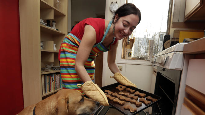 """In this Saturday, Dec. 15, 2012 photo, New York pet columnist for the magazine """"Everyday with Rachael Ray,"""" Sarah Zorn and her dog Rowdy pose for photos with her gingerbread holiday dog biscuits, in her home in Brooklyn, N.Y. The holidays might be the easiest time of the year to cook for dogs because human menus can be so easily adapted to their needs, said Zorn. (AP Photo/Richard Drew)"""