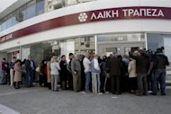Customers queue up outside a branch of Laiki Bank as they wait for the reopening of the bank in Nicosia March 28, 2013. REUTERS/Yorgos Karahalis