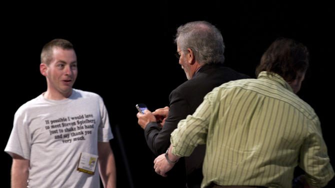 """Steven Spielberg, center, gets ready to take a picture of a fan who asked a question from the audience wearing a t-shirt that read, """"If possible I would love to meet Steven Spielberg just to shake his hand and say thank you very much.""""  during the panel for """"The Adventures of Tin Tin"""" during Comic Con  Friday, July 22, 2011, in San Diego. Peter Jackson moves past Spielberg at right.  (AP Photo/Gregory Bull)"""