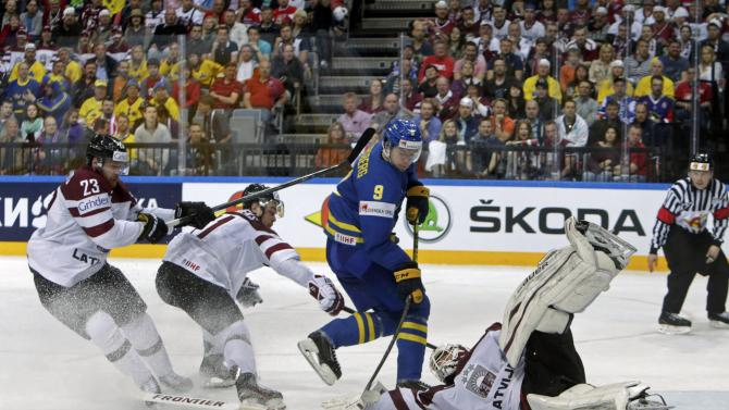 Latvia's goaltender Masalskis saves in front of Sweden's Forsberg during their Ice Hockey World Championship game at the O2 arena in Prague
