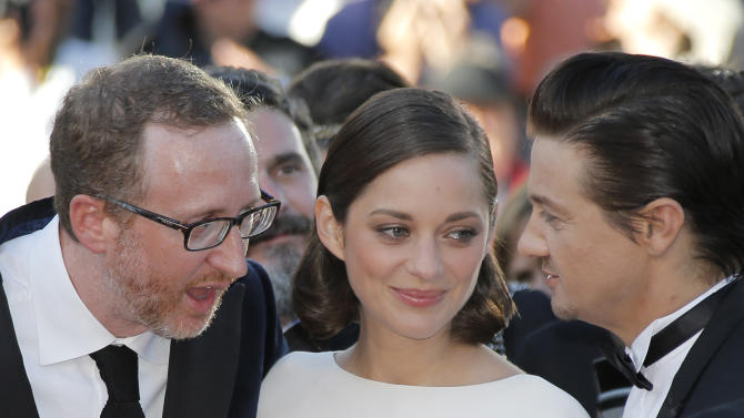 From left, director James Gray, actress Marion Cotillard, and actor Jeremy Renner speak as they arrive for the screening of The Immigrant at the 66th international film festival, in Cannes, southern France, Friday, May 24, 2013. (AP Photo/Lionel Cironneau)