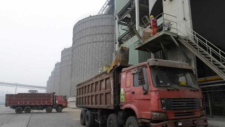 Workers fill trucks with soybeans at a port in Rizhao