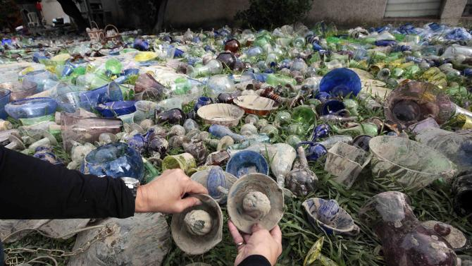 A woman cleans and sorts glass creations from the Biot Glass Factory damaged after flooding caused by torrential rain in Biot
