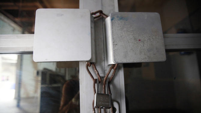 The entrance of This Day newspaper padlocked, as workers barricaded the office due to non payment of salaries  in Lagos, Nigeria, Friday, May 10, 2013. Known more for bringing in celebrities and smiling in photographs next to former Western leaders, a flamboyant Nigerian newspaper publisher now faces a challenge from his most vocal critics _ his own employees. Workers have barricaded the front of This Day newspapers in Lagos, hoping to force publisher Nduka Obaigbena into paying them as much as four months' worth of back salaries due to them. Back pay disputes often hit industries in Nigeria, a country where steady paying jobs remain few, but this crisis has hit a man politically connected to the nation's ruling elite, the second such major business figure to be stung in recent months (AP Photos/Sunday Alamba)