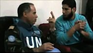 An image grab taken from a video uploaded on YouTube purportedly shows Moroccan UN observer, Colonel Ahmed Himmiche, speaking Abdul Razzaq Tlas (R), leader of the opposition Katibat al-Faruqin, during his visit to the restive central city of Homs
