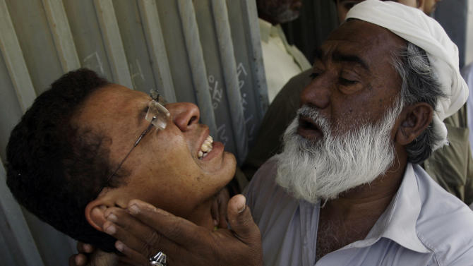 An unidentified man comforts Ali Mohammad, mourning the death of his father killed in a bomb blast, outside his residence in Karachi, Pakistan on Monday, Nov. 26, 2012. A bomb hidden in a cement construction block exploded in the southern city of Karachi killing at least one person and injuring several others, a police official said. (AP Photo/Shakil Adil)