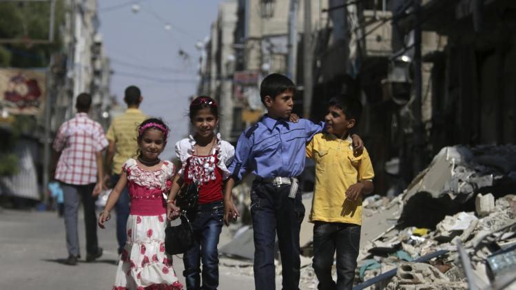 Children walk past debris along street during Eid al-Fitr in Duma, eastern al-Ghouta, near Damascus