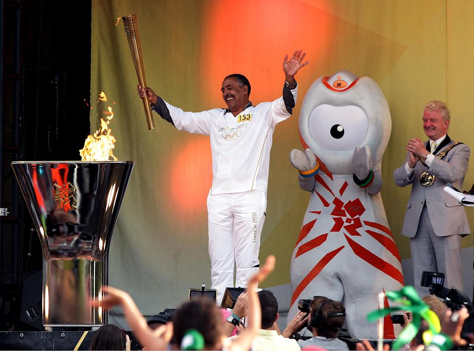 In this photo provided by LOCOG, torchbearer 153 Daley Thompson acknowledges the crowd after lighting the cauldron at the end of Day 68 in the Torch Relay on Wednesday July 25, 2012, in London. (AP Photo/LOCOG, Yui Mok)