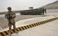 A US soldier stands guard as Afghanistan&#39;s Public Protection Forces (APPF) soldiers stand to attention on a base on the outskirts of Kabul on March 15, 2012. Teh US is seeking to ensure any remaining soldiers in Afghanistan will have immunity from prosecution in local courts