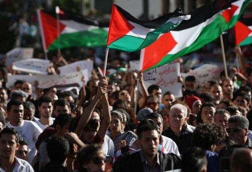 Palestinian demonstrators hold national flags in the West Bank city of Ramallah