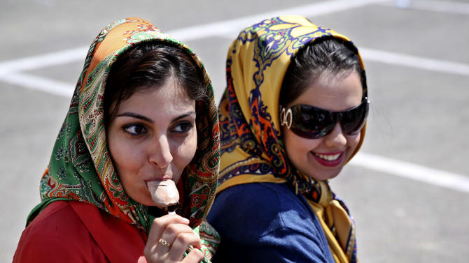 An Iranian woman eats ice-cream during a ceremony to unveil 5-tons of ice-cream at the Tochal mountainous area, of northern Tehran, Iran, Monday, April 1, 2013. Choopan dairy unveiled 5-tons of chocolate ice-cream, the largest in the world, according to the factory officials. (AP Photo/Ebrahim Noroozi)