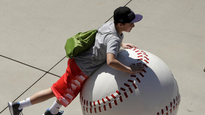 A youngster plays on a large concrete baseball before a  spring training baseball game between the Seattle Mariners and the San Diego Padres Thursday, March 5, 2015, in Peoria, Ariz. (AP Photo/Charlie Riedel)