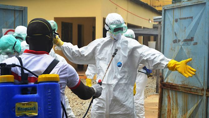 Guinea Red Cross health workers wearing protective suits prepare to carry the body of an Ebola victim at the Medecin sans frontieres Ebola treatement centre near the Donka hospital in Conakry on September 14, 2014