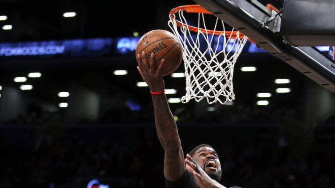 Toronto Raptors' Amir Johnson (15) goes to the basket against Brooklyn Nets' Brook Lopez, left, and Cory Jefferson (21)  during the first quarter of an NBA basketball game Friday, Jan. 30, 2015, in New York. (AP Photo/Jason DeCrow)