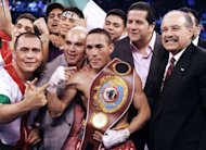 Mexico's Juan Francisco Estrada (C) celebrates with his team after beating Brian Viloria of the US during their WBO/WBA world flyweight title bout at the 'Fists of Gold' boxing event in Macau on April 6, 2013