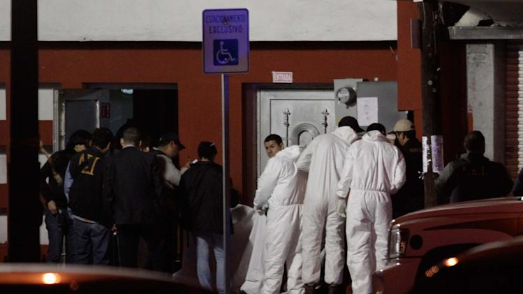 Forensic technicians inspect the body of a man at the entrance of a night club in Monterrey