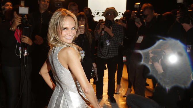 Actress Kristin Chenoweth poses for photographers as she stands on the runway before the Project Runway show at Fashion Week