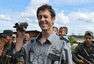 French journalist Romeo Langlois smiles and takes video images after being by the Revolutionary Armed Forces of Colombia (FARC) to a humanitarian mission