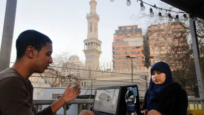 Egyptians log on to the Internet at a community center in front of a mosque in Cairo, Egypt, Saturday, Feb. 9, 2013. A Cairo court on Saturday ordered the government to block access to the video-sharing website YouTube for 30 days for carrying an anti-Islam film that caused deadly riots across the world. (AP Photo/Amr Nabil)