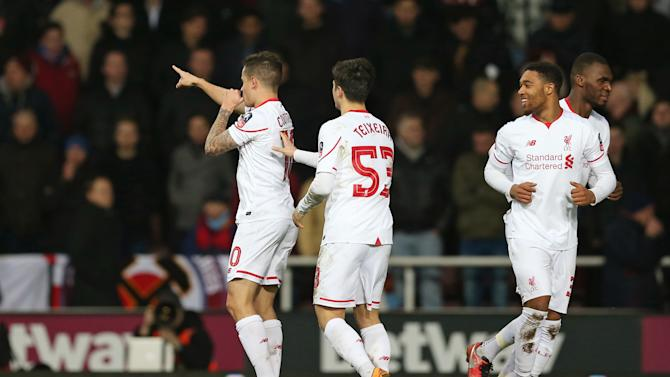 Philippe Coutinho celebrates with team mates after scoring the first goal for Liverpool