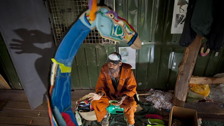 In this photo taken Monday, April 29, 2013, Jackson Mbatha, 40, sits with some of the discarded flip-flops he will carve up and glue together to make a large giraffe, at the Ocean Sole flip-flop recycling company in Nairobi, Kenya. The company is cleaning the East African country's beaches of used, washed-up flip-flops and the dirty pieces of rubber that were once cruising the Indian Ocean's currents are now being turned into colorful handmade giraffes, elephants and other toy animals. (AP Photo/Ben Curtis)