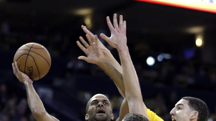 San Antonio Spurs' Tony Parker, left, shoots between Golden State Warriors' David Lee (10) and Klay Thompson, right, during the first half of an NBA basketball game Friday, Feb. 22, 2013, in Oakland, Calif. (AP Photo/Ben Margot)