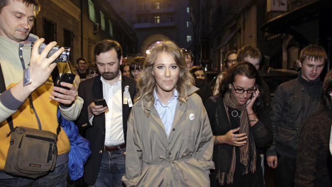"FILE - In this Tuesday, May 8, 2012 file photo Russian socialite and TV host Ksenia Sobchak, center, daughter of the late St. Petersburg mayor, Anatoly Sobchak, and Russian parliament member Ilya Ponomarev, second left, walk with protesters in downtown Moscow, a day after Putin's inauguration.""I'm Ksenia Sobchak, and I've got something to lose. But I'm here."" This is what the 30-year-old blond socialite and TV personality said when she began her unlikely foray into political activism by taking the stage at a huge anti-Putin rally in December. Once considered untouchable because of her family's close personal ties to President Vladimir Putin, Sobchak has since found that she does indeed have something to lose, as her apartment has been raided by police and she has been called in for interrogation. It has been a quick change of fortune for Russia's It Girl, who like many Russians of her generation experienced a civic awakening after many years of political passivity. (AP Photo/Sergey Ponomarev, file)"