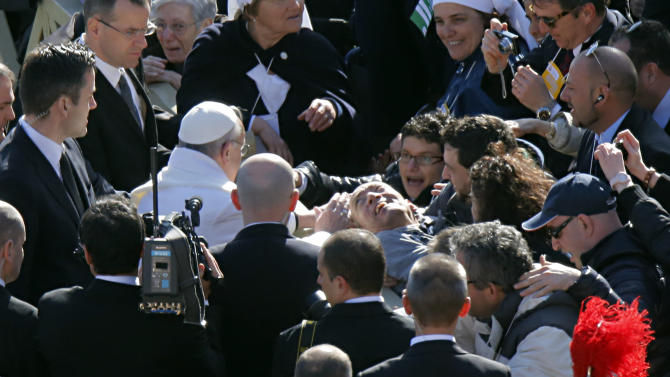 Pope Francis blesses a man prior to his inaugural Mass, in St. Peter's Square at the Vatican, Tuesday, March 19, 2013. Pope Francis thrilled tens of thousands of people on Tuesday gathered for his installation Mass, taking a long round-about through St. Peter's Square and getting out of his jeep to bless a disabled man in a wheelchair in the crowd. (AP Photo/Dmitry Lovetsky)