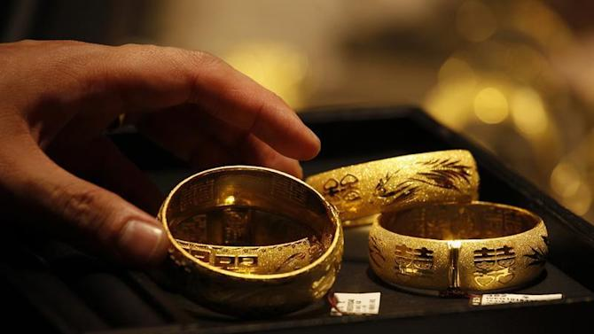 Shop attendant shows 24K gold bracelets inside jewellery store in Hong Kong