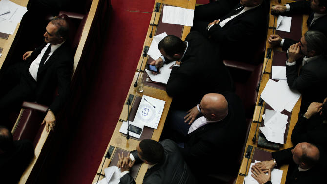 Lawmaker Ilias Panagiotaros, center, of the extreme right Golden Dawn party, sketches his party logo on a piece of paper during a debate in Parliament session in Athens early Friday Jan. 18, 2013. The party sought an investigation of two former prime ministers over an emerging scandal involving the handling by authorities of data on Greeks with Swiss bank accounts. Lawmakers rejected the proposal but voted by an  overwhelming majority to investigate former finance minister George Papaconstantinou _ a probe backed by all political parties in the 300-member assembly. (AP Photo/Petros Giannakouris)