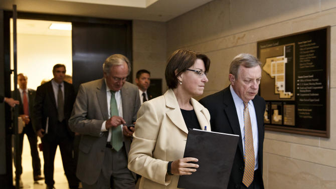 FILE - In this Wednesday, June 4, 2014 file photo, Sen. Amy Klobuchar, D-Minn., center, Senate Majority Whip Dick Durbin, D-Ill., right, and other senators emerge from a closed-door briefing with intelligence officials about the Obama administration's decision to swap five members of the Taliban for captive Army Sgt. Bowe Bergdahl, at the Capitol in Washington. Democrats with presidential dreams for 2016 are coming to Iowa in 2014 with little fanfare, entourage or recognition. They are undeterred by talk of a Clinton candidacy or her plans to visit the leadoff caucus state in September 2014 to honor retiring Sen. Tom Harkin. Klobuchar's scheduled trip to Iowa on Saturday, Aug. 23, 2014 is to be her third since the 2012 election. (AP Photo/J. Scott Applewhite)