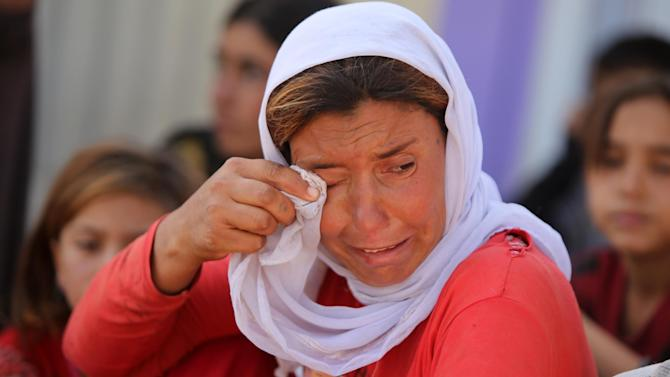 A displaced Iraqi Yazidi woman wipes her eyes at the Bajid Kandala camp near the Tigris River, in Kurdistan's western Dohuk province, where they took refuge after fleeing advances by Islamic State jihadists in Iraq on August 13, 2014