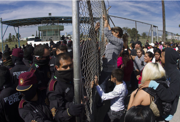 Police hold back the relatives of inmates outside Apodaca correctional state facility as they try to get past the gates in Apodaca on the outskirts of Monterrey, Mexico, Sunday Feb. 19, 2012. A fight