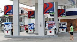 Woman walks past a petrol station that is closed due …