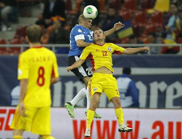 Taijo Teniste, left, of Estonia and Gheorghe Bucur of Romania, right, jump for a header during the World Cup Group D qualifying soccer match at the National Arena stadium in Bucharest, Romania, Tuesda