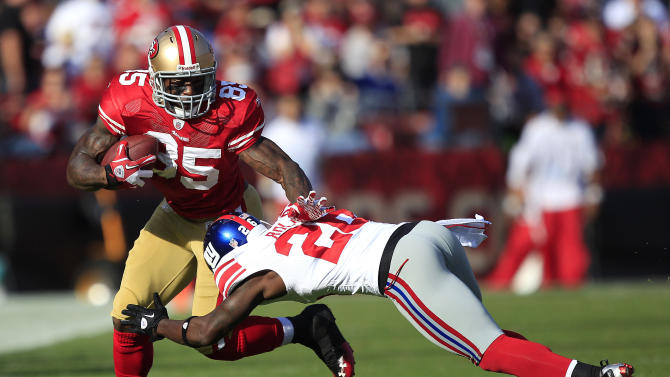 San Francisco 49ers tight end Vernon Davis (85) runs with a reception against New York Giants free safety Antrel Rolle (26) in the second quarter of an NFL football game in San Francisco, Sunday, Nov. 13, 2011. (AP Photo/Marcio Jose Sanchez)