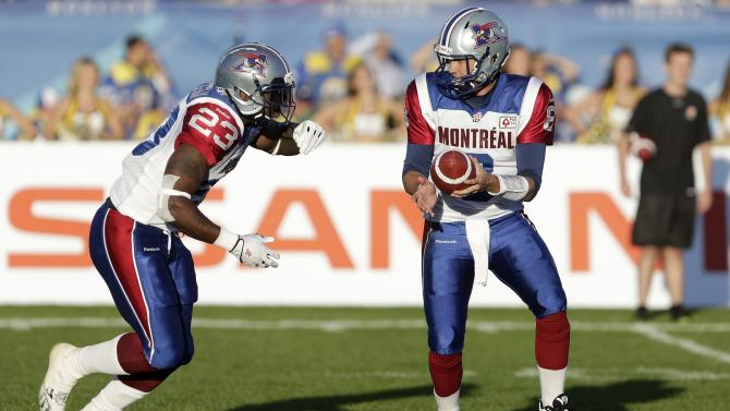 Montreal Alouettes quarterback Neiswander hands off the football to running back Messam during the first half of the 2013 CFL Touchdown Atlantic game against the Hamilton Tiger-Cats in Moncton