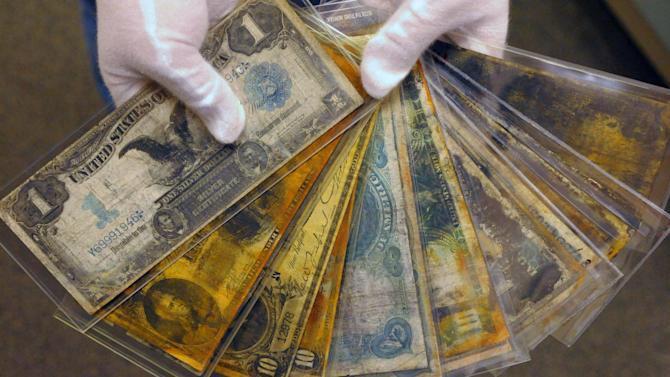 FILE - In a Friday, Aug 15, 2008 file photo, currency, part of the artifacts collection of the Titanic, is shown at a warehouse in Atlanta. The owner of the largest trove of artifacts salvaged from the Titanic is putting the vast collection up for auction as a single lot in 2012, the 100th anniversary of the world's most famous shipwreck. The auction is scheduled for April 1 by Guernsey's, a New York City auction house, according to filings by Premier Exhibitions Inc. with the Securities and Exchange Commission. A spokeswoman for the auction house and Premier Exhibitions declined Wednesday Dec. 28, 2011 to discuss the auction with The Associated Press until a formal announcement in January.  (AP Photo/Stanley Leary, File)