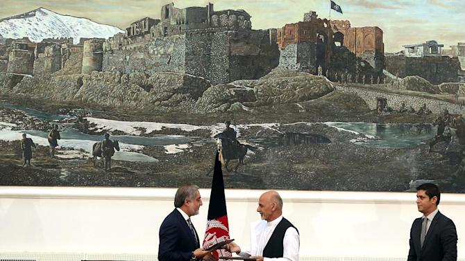 Afghanistan's presidential election candidates Abdullah Abdullah, left, and Ashraf Ghani Ahmadzai, center hold their documents after signing a power-sharing deal at presidential palace in Kabul, Afghanistan, Sunday, Sept. 21, 2014. Afghanistan's two presidential candidates signed a power-sharing deal Sunday, capped with a hug and a handshake, three months after a disputed runoff that threatened to plunge the country into turmoil and complicate the withdrawal of U.S. and foreign troops. (AP Photo/Massoud Hossaini)