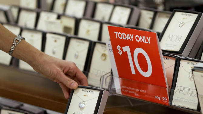 In this Friday, Nov. 23, 2012 photo, a woman browses through a display of jewelry on sale at a J.C. Penney store in Las Vegas. In the midst of the busy holiday shopping season, when retailers can make up to 40 percent of their sales, promotions are actually down 5 percent year over year so far, according to BMO Capital market's sales rack index. (AP Photo/Julie Jacobson)
