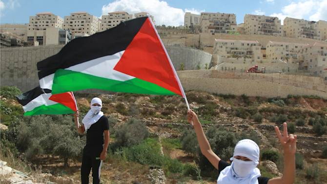 Palestinian protesters wave the national flag, in front of the Israeli settlement of Beitar Illit on September 26, 2014