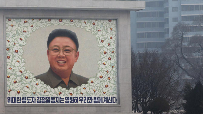 North Koreans pay respect in front of a mosaic of the late North Korean leader Kim Jong Il on the eve of his first death anniversary in Pyongyang, North Korea, Sunday, Dec. 16, 2012. (AP Photo/Ng Han Guan)