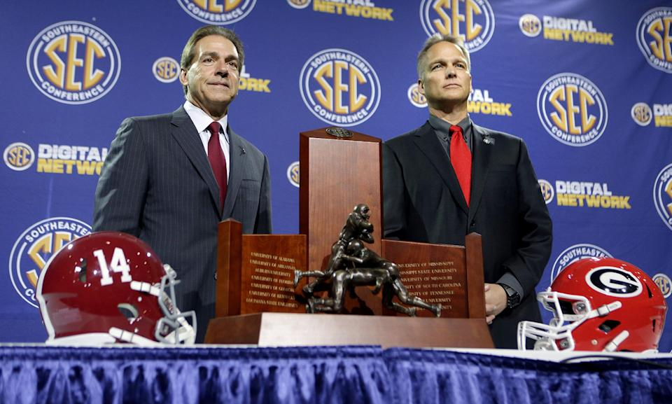 Alabama head coach Nick Saban, left, and Georgia head coach Mark Richt, pose for a photo with the Southeastern Conference championship trophy during a news conference ahead of Saturday's SEC Championship NCAA college football game, Friday, Nov. 30, 2012, in Atlanta. (AP Photo/David Goldman)