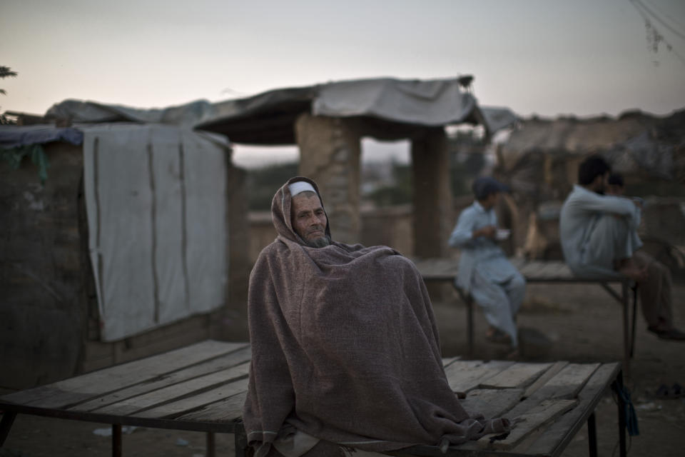 An elderly Pakistani man, who was displaced with his family from Pakistan's tribal areas due to fighting between the Taliban and the army, wraps himself with a shawl while sitting outside a mosque on the outskirts of Islamabad, Pakistan, Saturday, Nov. 2, 2013. (AP Photo/Muhammed Muheisen)