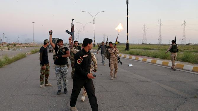 """Iraqi security forces chant slogans against the Islamic State group as they open the main road between Baghdad and Tikrit, 80 miles (130 kilometers) north of Baghdad, Iraq, Wednesday, April 1, 2015. Iraqi security forces battled the last remaining pockets of Islamic State militants in Tikrit on Wednesday and were expected to gain full control of the city """"within the coming hours,"""" said Iraqi Interior Minister Mohammed Salem al-Ghabban. (AP Photo/Khalid Mohammed)"""