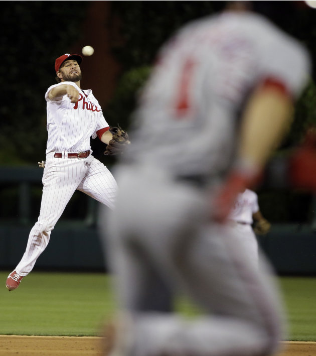 Philadelphia Phillies second baseman Kevin Frandsen, left, throws to first base on a ground out by Washington Nationals' Stephen Lombardozzi in the eighth inning of a baseball game, Wednesday, June 19